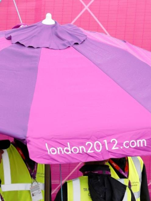 Workers shelter from rain under a parasol in the London 2012 Olympic Park at Stratford in London...