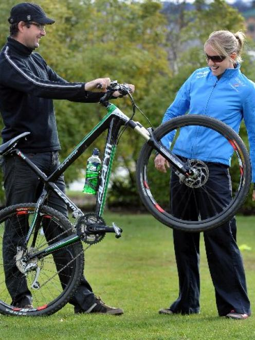 World champion cyclist Alison Shanks examines her mountain bike with partner Craig Palmer before...
