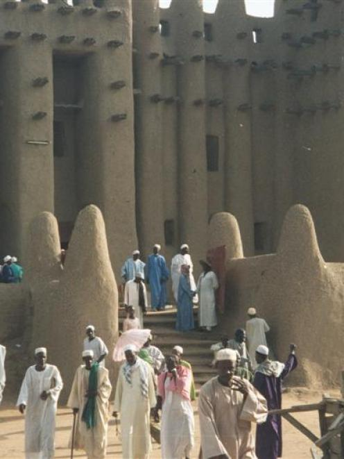 Worshippers (left) stream out of the grand mosque at Djenne. Photo by Alistair McMurran.