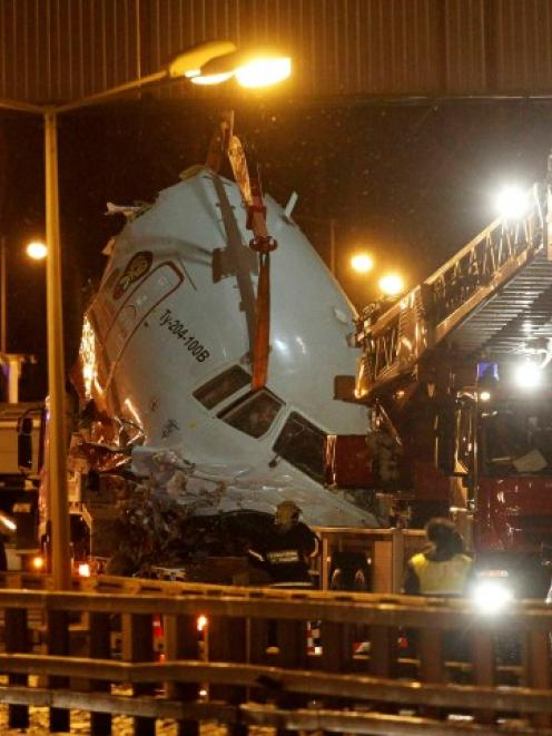Wreckage is removed from a highway near Moscow's Vnukovo airport where an airliner split into...