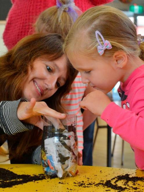 Xanthe White helps Evangeline Clarke (3) plant a broad bean in a recycled plastic bottle during a...
