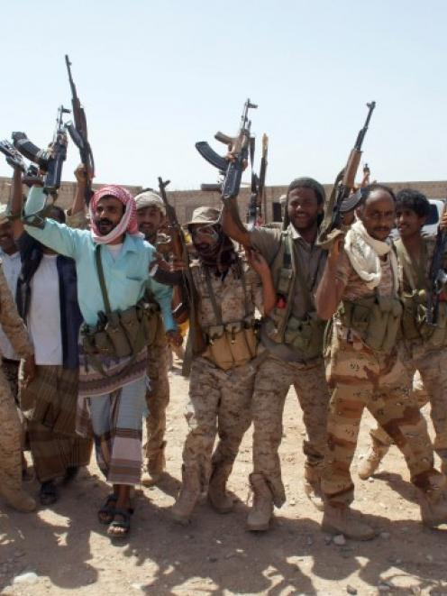 Yemeni soldiers hold up their weapons at a position taken from al Qaeda militants in Mayfaa, in...