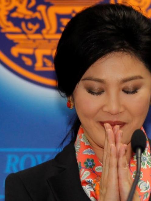 Yingluck Shinawatra gives a traditional greeting as she addresses reporters in Bangkok. REUTERS...