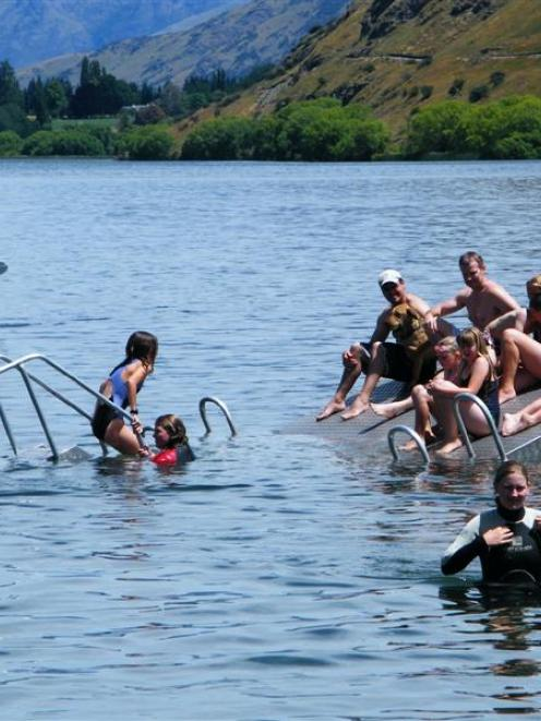 Young holidaymakers continue to use the damaged and half submerged pontoon, at Lake Hayes,...