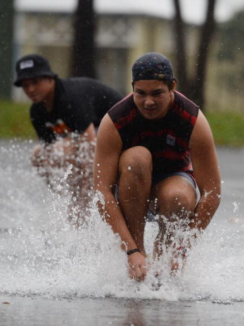 Young men ride skateboards through pools of water formed by heavy rain before Cyclone Ita makes...