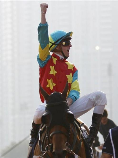 Zac Purton  cheers after winning the Hong Kong Mile on Ambitious Dragon at Sha Tin on Sunday....