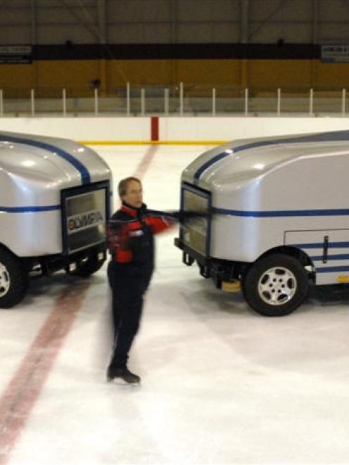 Dunedin ice skating coach Fanis Shakirzianau has a spin in front of the two resurfacing machines...