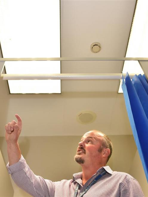 Facilities and site development manager Warren Taylor points to a retrofitted ceiling in the...