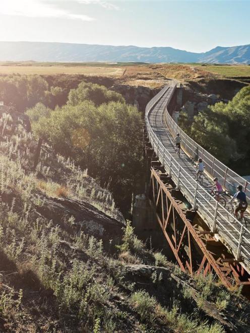 Cyclists cross a bridge on the Otago Central Rail Trail. Photo supplied.