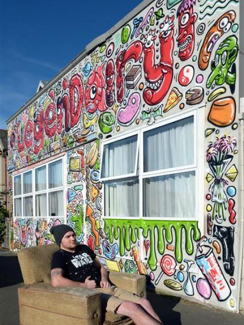 University of Otago student Nathan Laurie sits in front of his freshly painted Duke St flat....