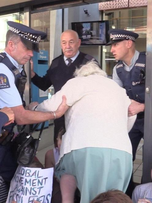 Police help Margaret Saunders into the bank on Thursday. Photo by Craig Baxter.