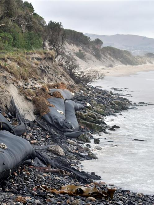 The protective sand sausages at Ocean Beach sit exposed to the sea again yesterday after months...