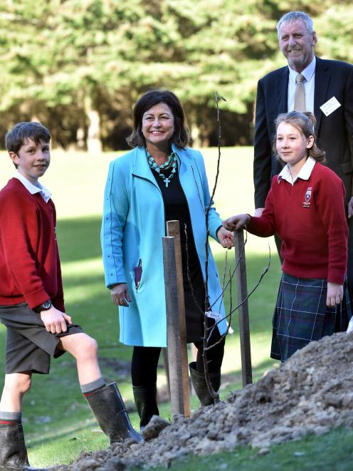 Education Minister Hekia Parata helps Kaikorai Valley College pupils Jack Hitchcox (12), Jessica Power (11) and principal Rick Geerlofs plant an apple tree on the school's urban farm. Photo by Peter McIntosh.