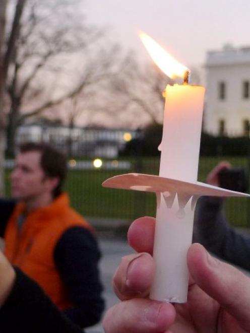 Supporters of gun control legislation hold candles during a rally in front of the White House in...