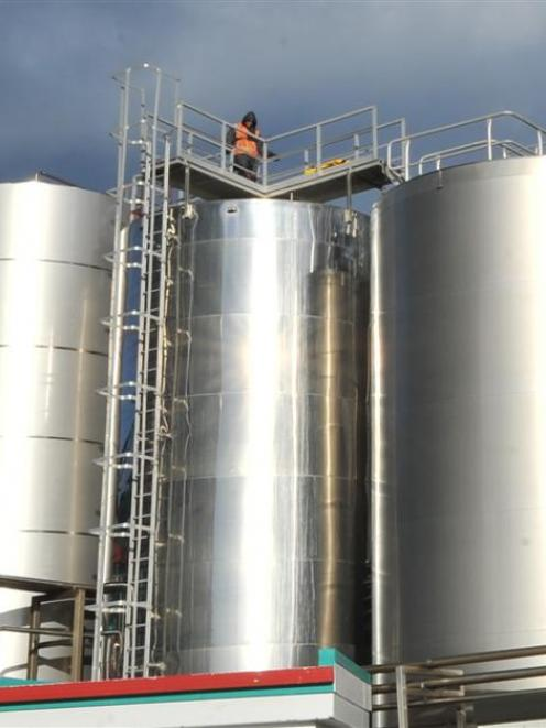 A contractor stands on top of the silo as workers abseil inside.