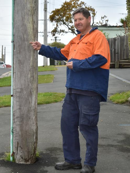 Eric Gotlieb is concerned about the safety of several power poles in his neighbourhood. Photo by Gregor Richardson.