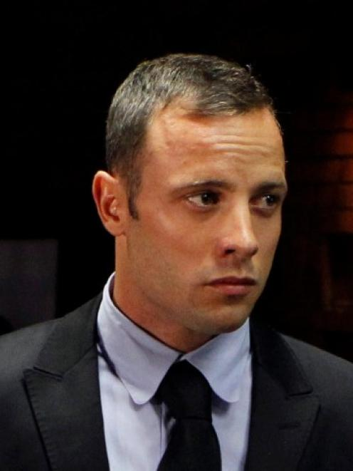 Oscar Pistorius stands in the dock during a break in court proceedings at the Pretoria...