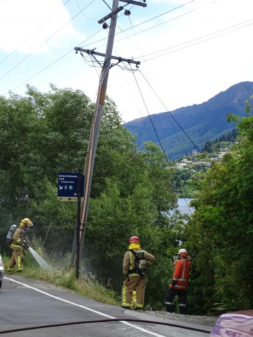 Volunteer firefighters fight a fire sparked when an 11,000-volt power line came down in...