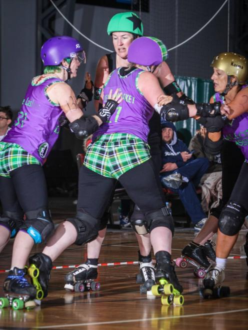 Charmaine Reveley, aka Little Yellow Jacket, (centre) gets a push in the back during a roller derby match. Photo supplied.