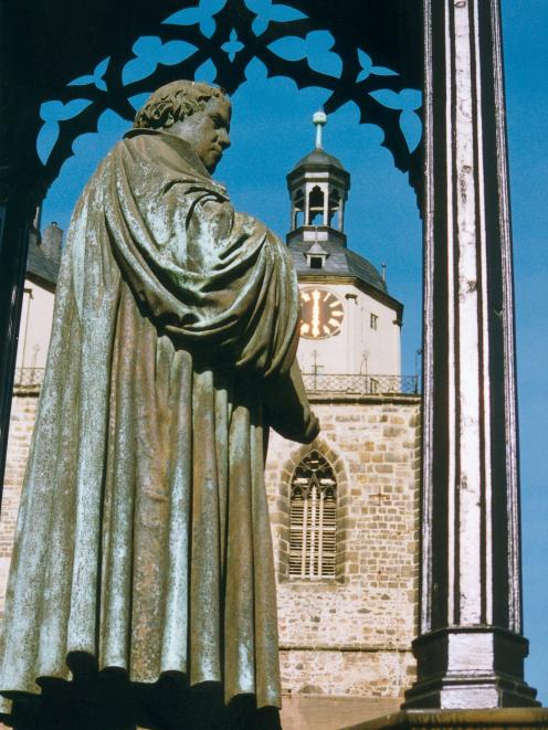 A statue in Wittenberg's market square depicts Martin Luther with a copy of the New Testament,...