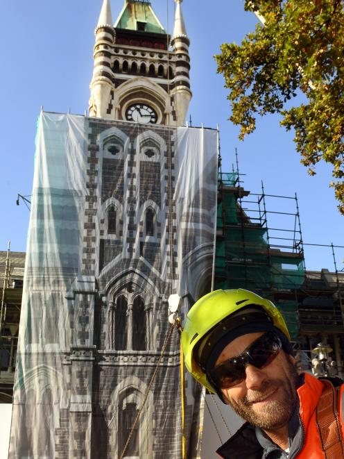 Adgraphix sales consultant Jono Gallacher in front of the clocktower after it was covered by a sheet of printed scrim for the benefit of graduates. Photo: Stephen Jaquiery.