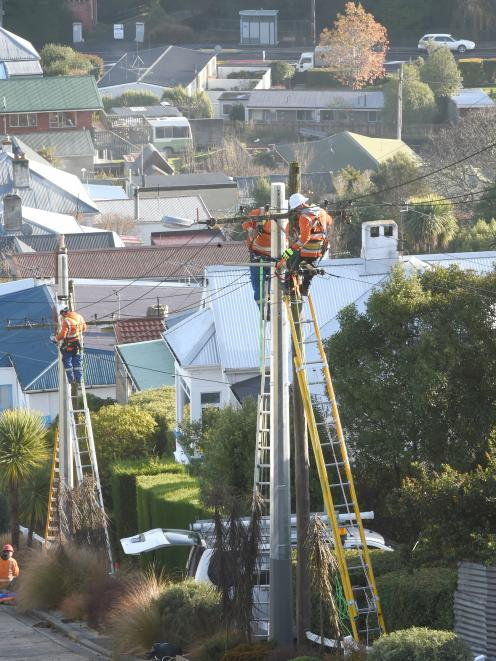 Contractors work to replace old power poles on Baldwin St yesterday. Photo: Gregor Richardson