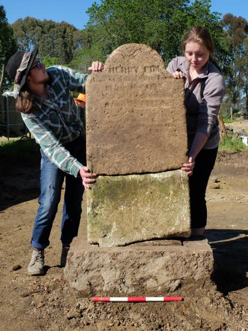 Archaeology students Teina Tutaki (left) and Alana Kelly hold up Henry Pim's headstone after it was found broken and buried at the St John's burial ground at Tokoiti. Photo: Supplied
