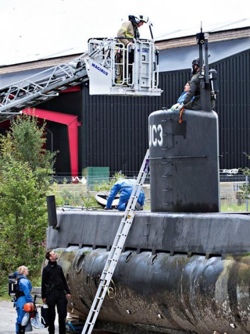 "Police technicians investigate the rescued private submarine ""UC3 Nautilus"" in Copenhagen. Photo: Reuters"