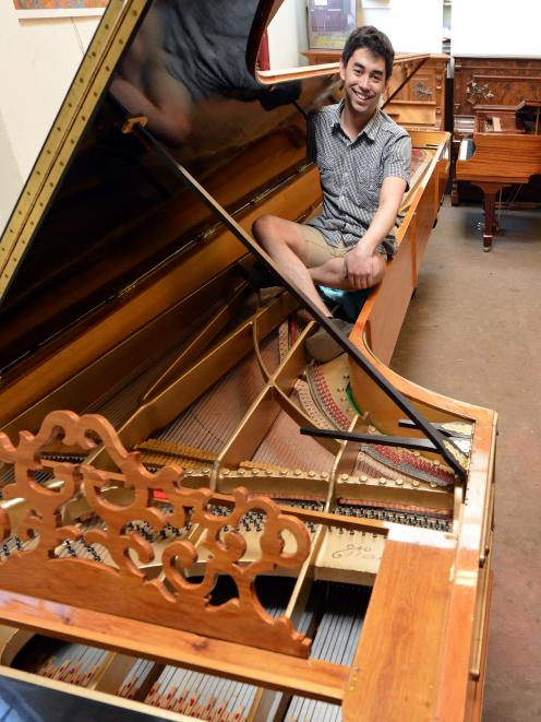 Alexander Pianos piano tuner Adrian Mann (28) inside what is believed to be the largest piano in...