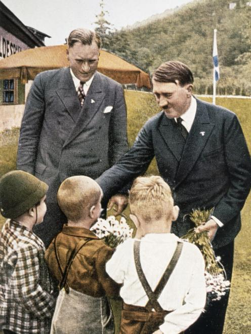 Nazi Party leader Adolf Hitler is handed flowers in a propaganda photograph. Photo: Hulton...