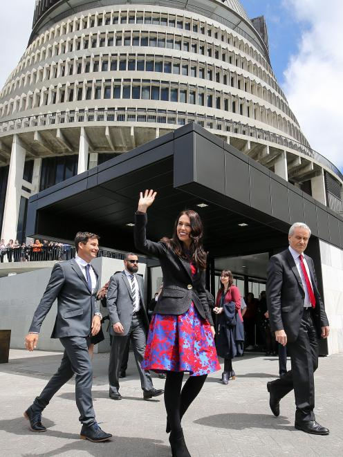 Prime Minister Jacinda Ardern, walking with partner Clarke Gayford, acknowledges the crowd outside parliament, in Wellington, yesterday. Photo: Getty Images