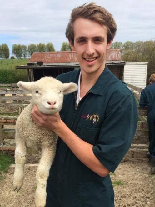 Veterinary science student Paul Blondell gets up close with a lamb. PHOTO: SUPPLIED