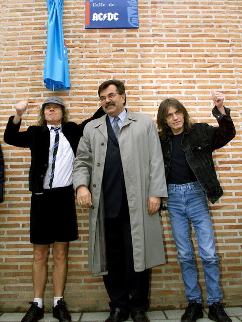 Angus and Malcolm Young (right), founder members of AC/DC, flank Jose Luis Perez. Photo: Reuters
