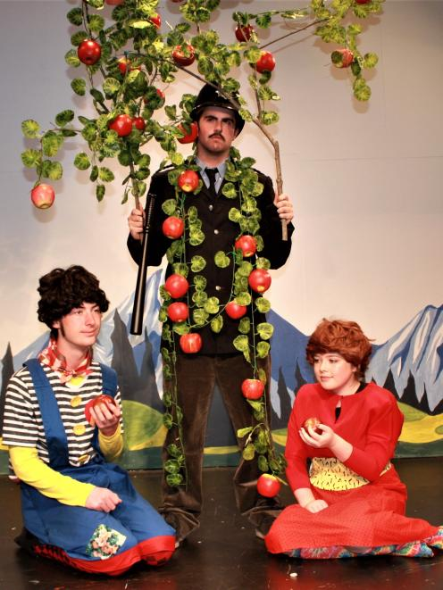 Badjelly the Witch characters Tim (Zac Henry, kneeling at left) and Rose (Tylah Harris) share the fruits offered by Nigel the apple tree (Rob Monzari) in a scene from Spike Milligan's delightfully bonkers comedy. Photo: Supplied