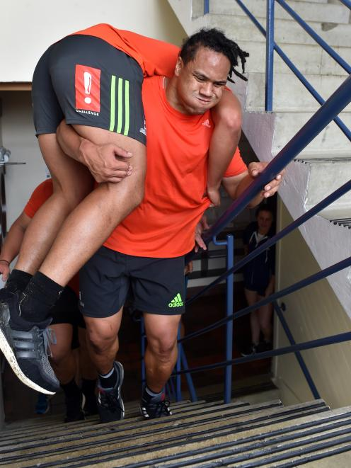 Highlanders prop Aki Seiuli carries lock Shannon Frizell up the stairs in the Richardson Building...