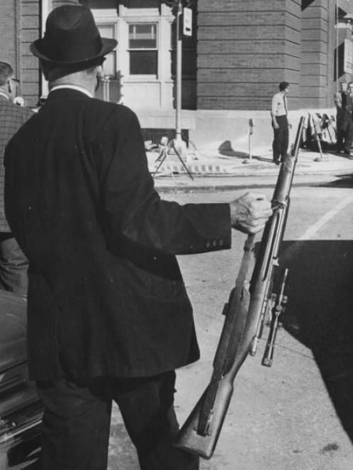 A man holding the rifle used by Lee Harvey Oswald after the assassination of the president John F...