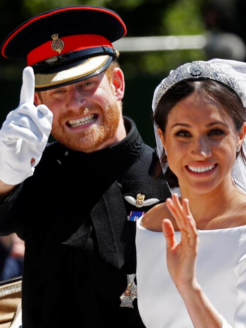 The Duke and Duchess of Sussex wave as they ride in a horse-drawn carriage after their wedding...