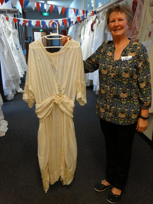 Iona Enliven Care Home activities co-ordinator Diane McCone with a wedding dress worn in 1920....