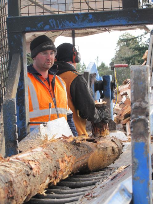 Ivan Murdoch and Alex Martin turning wet logs into wet firewood.