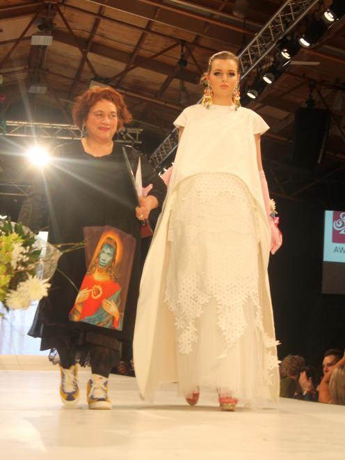 Designer Vicki Taylor-Blair, of Dunedin, walks down the runway alongside  a model wearing  her...