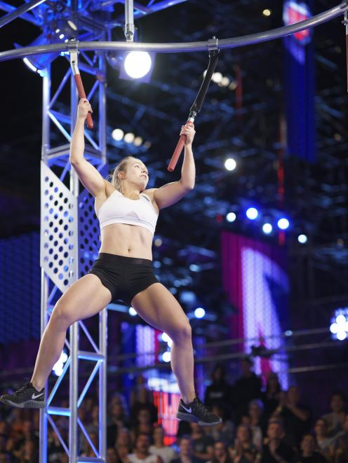 India Henry (22), formerly of Gore, holds on as she crosses through obstacles during season two of Ninja Warrior Australia. Photo: Supplied