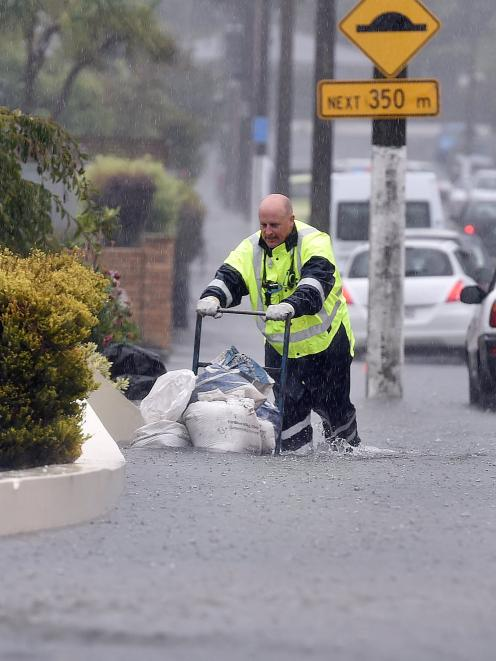 An emergency worker places sandbags at Radius Fulton rest-home during February flooding. Photo:...