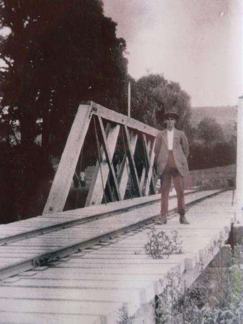 Tahakopa visitor H. Roxburgh poses on the bridge in this 1926 photograph.