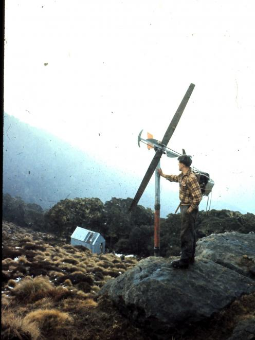 Barry Campbell checking the wind turbine he constructed to supply electricity to the ski hut...