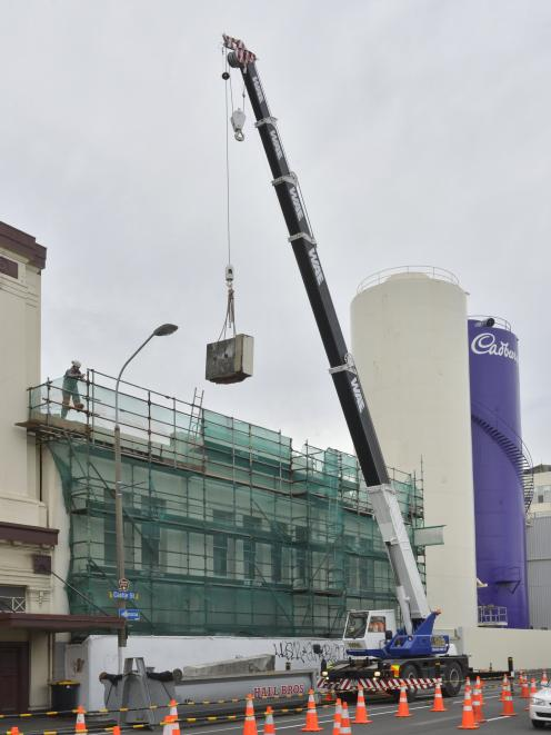 Workmen remove part of the parapet of building on the Cadbury site that had been being remodelled for use as Cadbury World. Photo: Gerard O'Brien