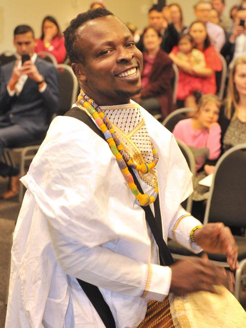 New citizen Robert Fugah, originally from Ghana, performs a traditional African drum song in front of the other new citizens at the end of a ceremony in the Glenroy Auditorium yesterday. Photo: Christine O'Connor
