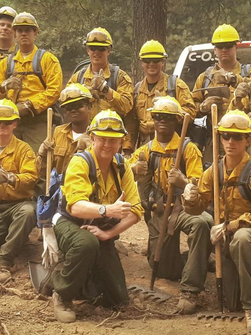 Te Anau rural firefighter Hamish Angus (centre front) with some of his US military firefighting...