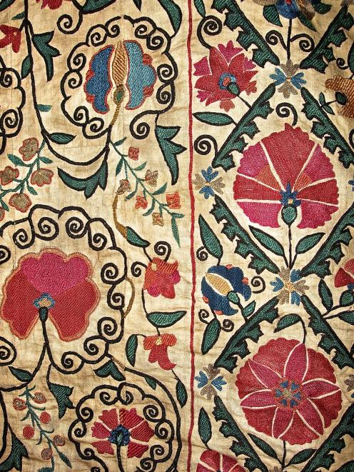 Detail of the embroidery, which depicts stylised regional flora.