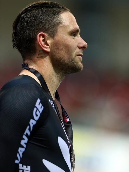 Eddie Dawkins, of New Zealand, stands on the podium after finishing second in the men's keirin at...