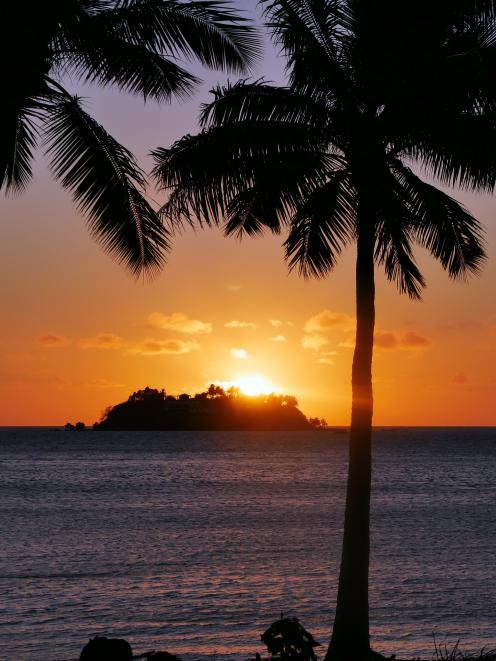 The sun sets behind the small island directly in front of a beachside bure at Tropica Island...